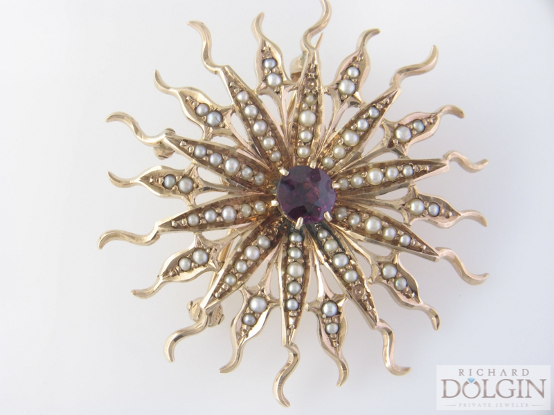 Antique gold pin featuring pearls and center garnet