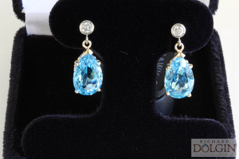 Blue topaz dangle earrings with bezel set round diamond