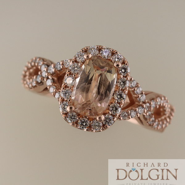 Top view of peach sapphire surrounded by diamonds