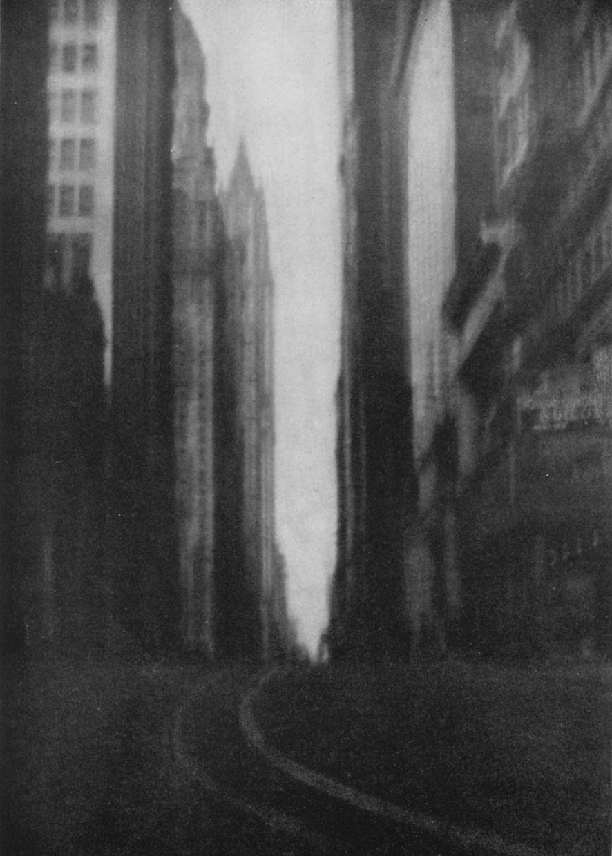 "ckck :     ""The Canyon"" by Jerry D. Drew, circa 1922.   There was no further description for this photo, but the pointed building looks like the Woolworth Building, which would place this photo in Lower Manhattan, New York City, on Broadway looking uptown.   In fact, it would've had to have been photographed right about  here , at the north end of Bowling Green, where the then-existing streetcar tracks of the Broadway Line would've curved, just like in the photo."