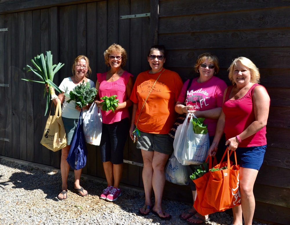 Happy customers are loaded up with freshly harvested vegetables from Elm Street Gardens.