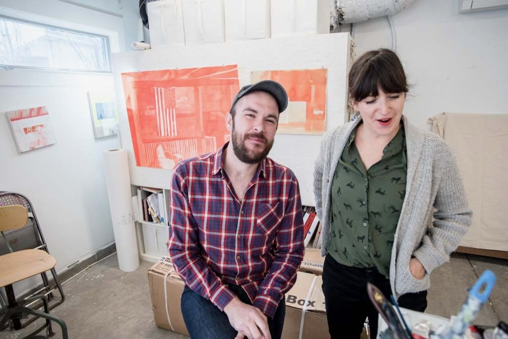 Jodi Hays and Matt Lovell in Jodi's studio in front of original ink wash painting of the security footage of Matt getting shot. Photo Credit: Eric England