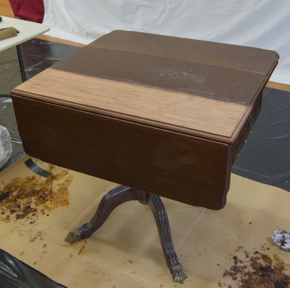 Simon stripped a thick two pack lacquer off this mahogany folding side table. You can see the piles of toffee like lacquer on the floor.