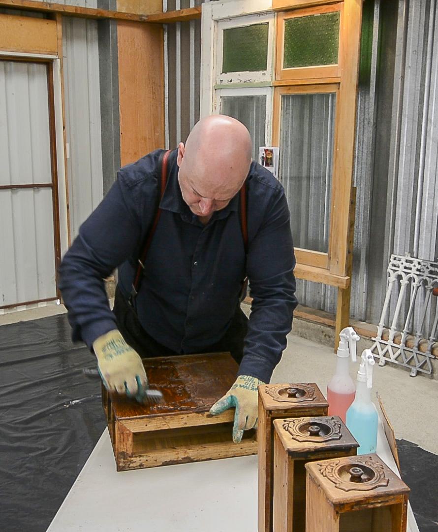 Simon using the detail brush to make short work of this shellacked singer drawer case.