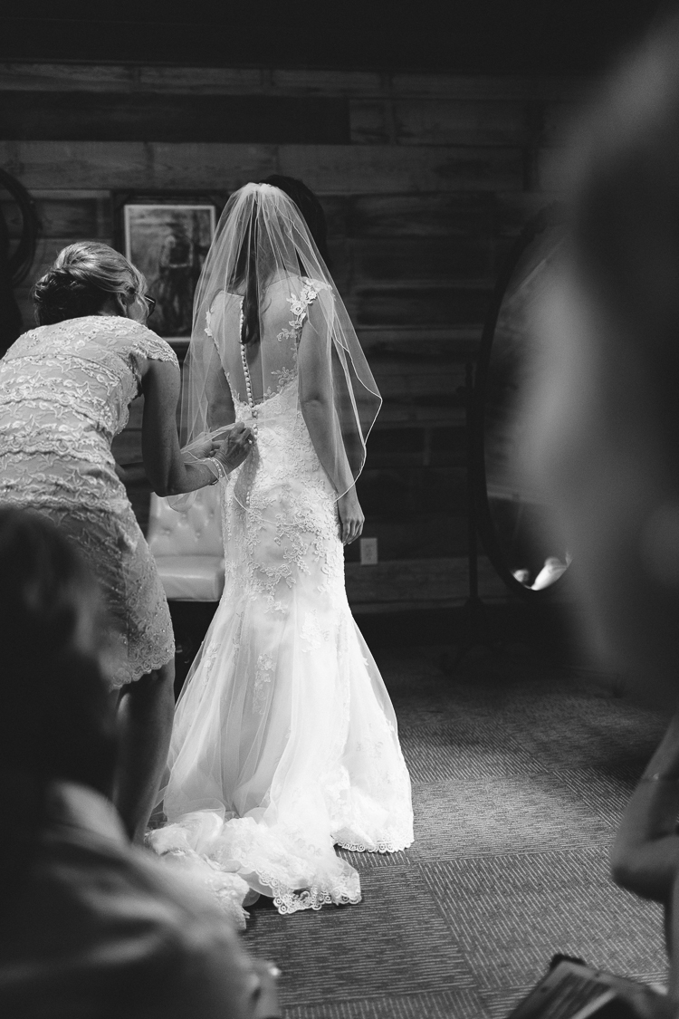 Black and White Shot of Bride putting on dress