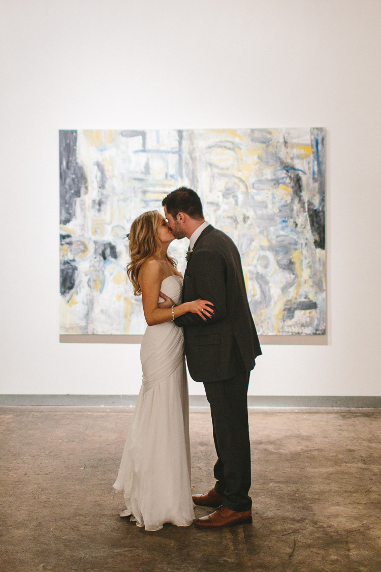 Bride and groom share a kiss at art gallery reception