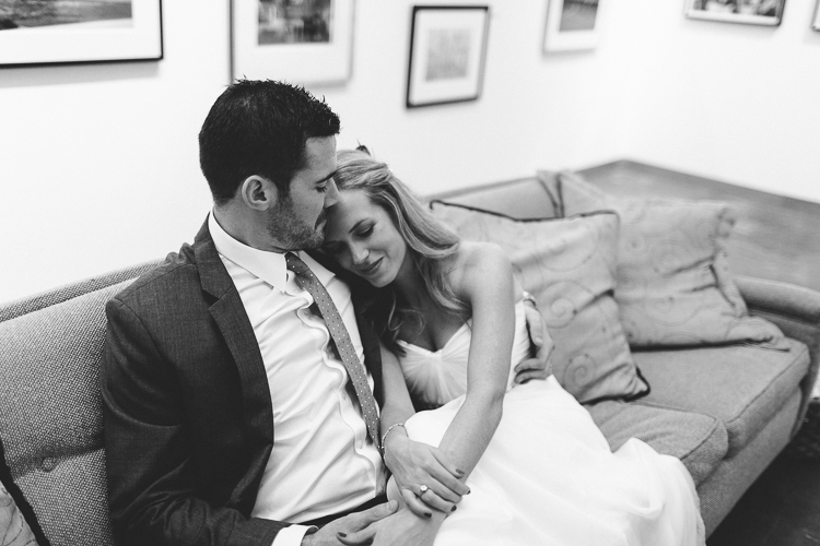 Bride and groom getting cozy at art gallery reception