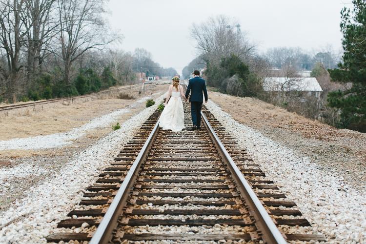 bride and groom walking on railroad tracks