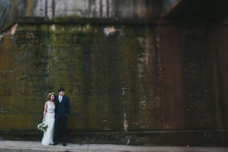 bride and groom by old concrete wall