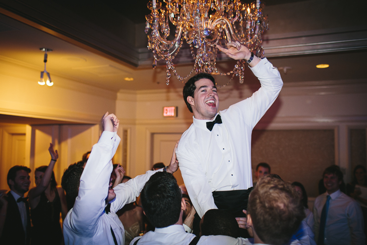 the groom gets lifted up at the wedding reception