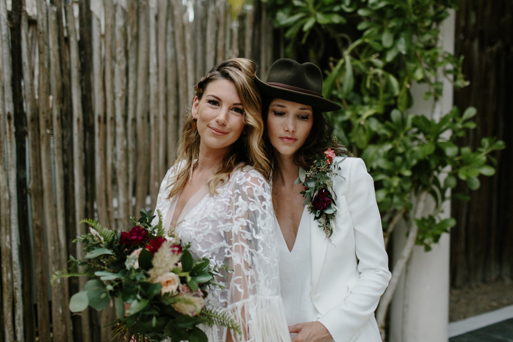Chelsea and Katie - TULUM DESTINATION WEDDINGCeremony: The Nest TulumEvent Design and Planning: Madeline SandlinFlorals: Moni JuncoWedding Dress: Meital Zano, Finery BoutiqueWhite Pant Suit: Alexander McQueen