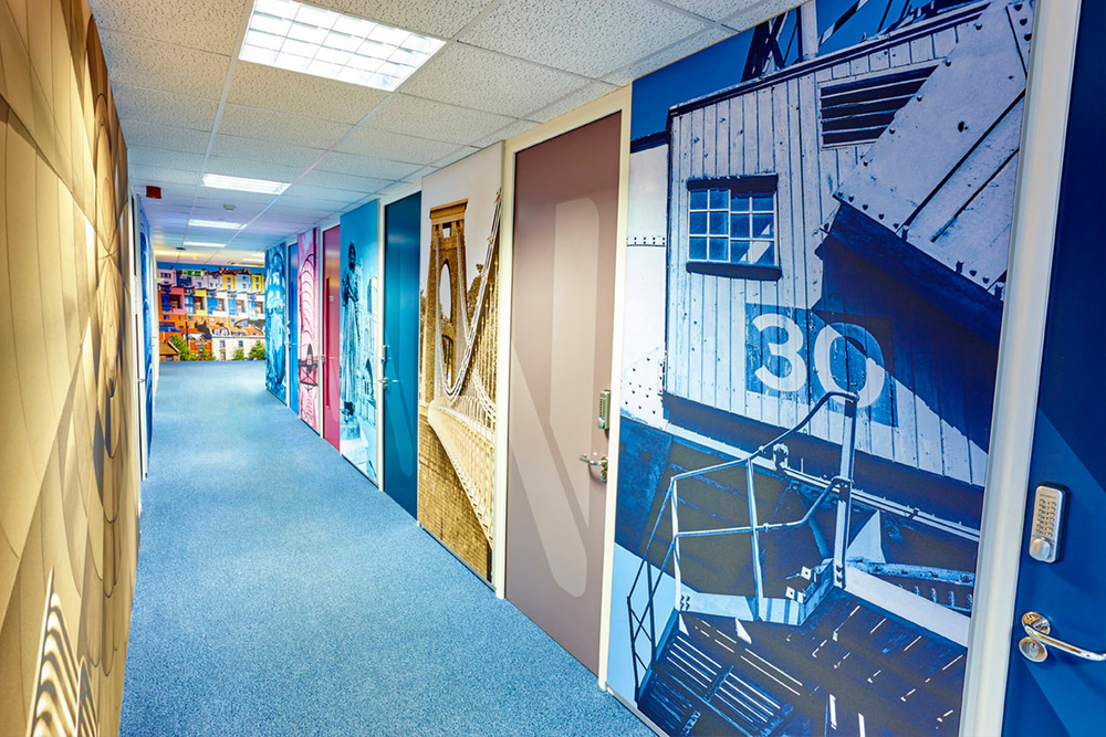 CORRIDOR AFTER  We refurbished the outdated doors with branded door graphics and continued the theme of local landmarks on Tension Fabric along the whole elevation.