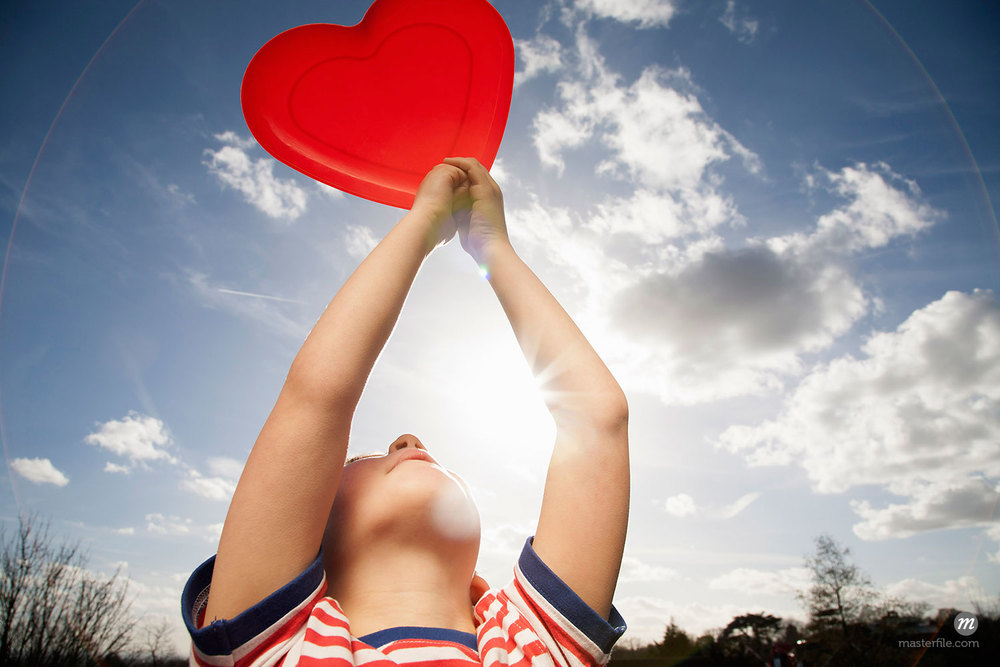 A child holding a red heart shape © Masterfile Royalty-Free (in Children Playing Outdoors)