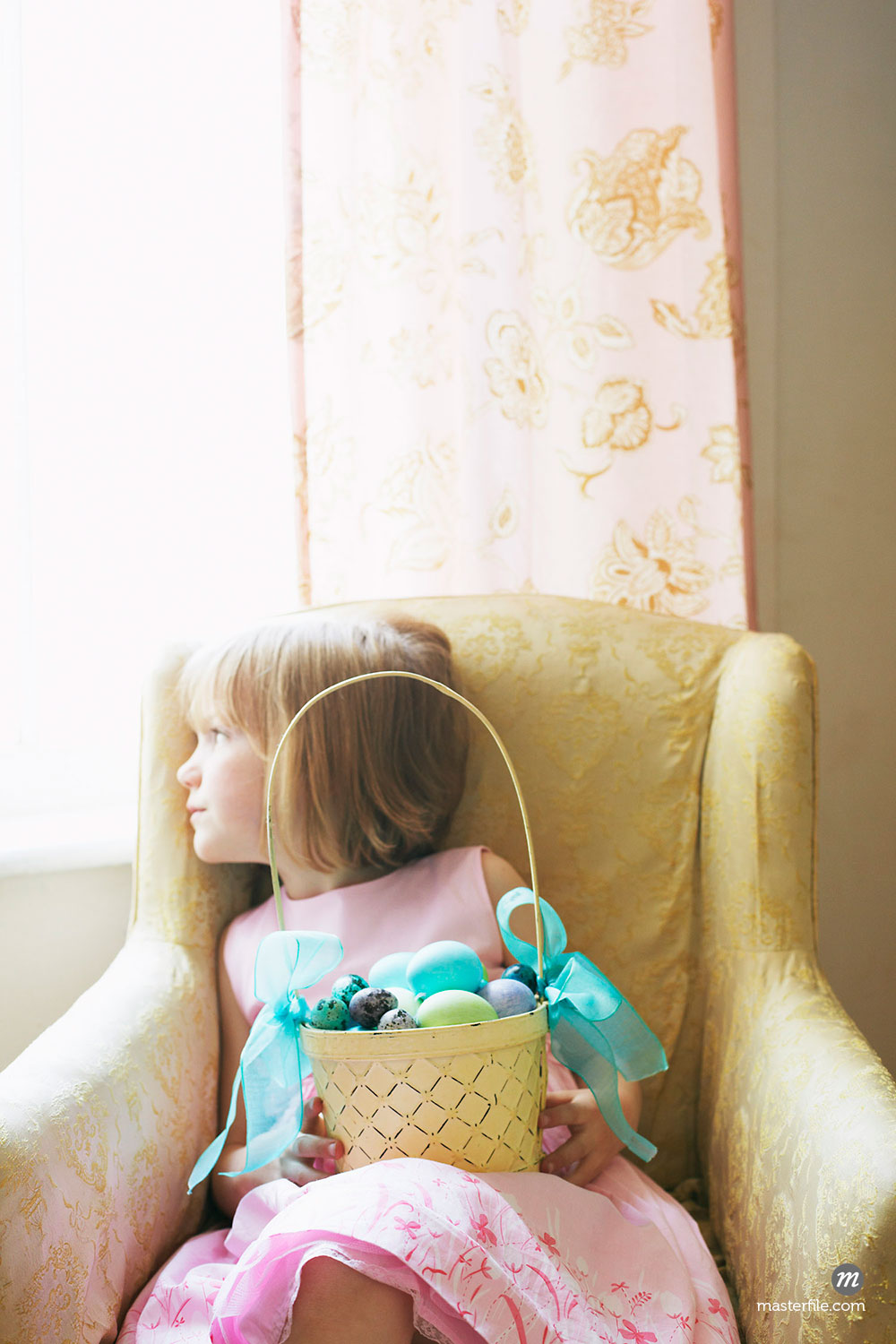 Girl Looking Out Window, Holding a Basket of Easter Eggs   ©  Susan Findlay / Masterfile