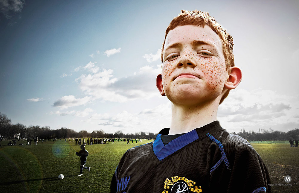Portrait of freckled boy on football pitch  ©  Cultura RM / Masterfile