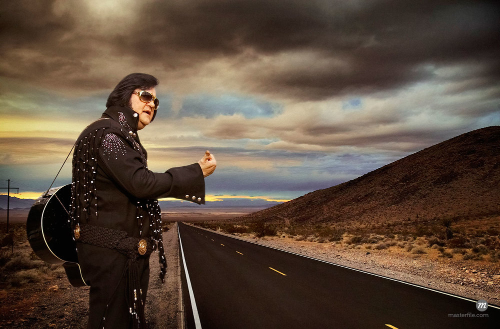 Elvis Impersonator Hitchhiking Under Dramatic Skies © George Simhoni / Masterfile