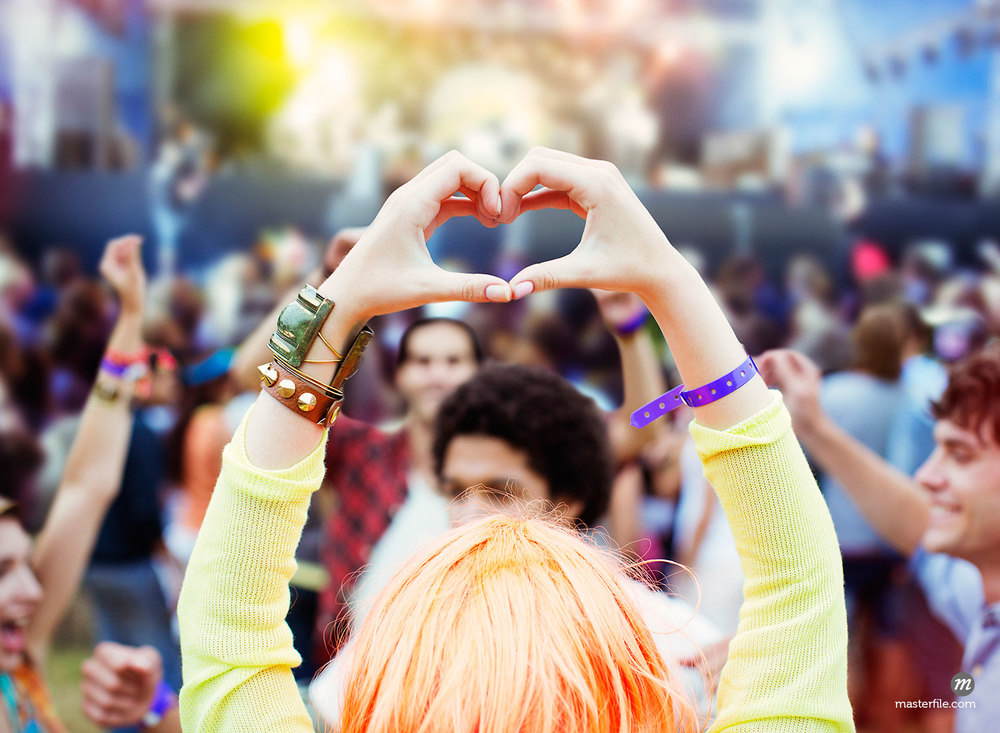 Woman forming heart-shape with hands at music festival  © Masterfile Royalty-Free (in  Youth Culture )