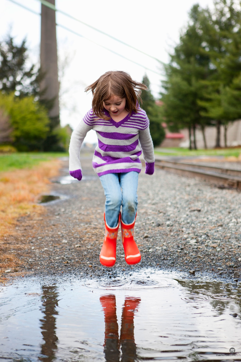 Girl Jumping in Puddle © Ty Milford / Masterfile