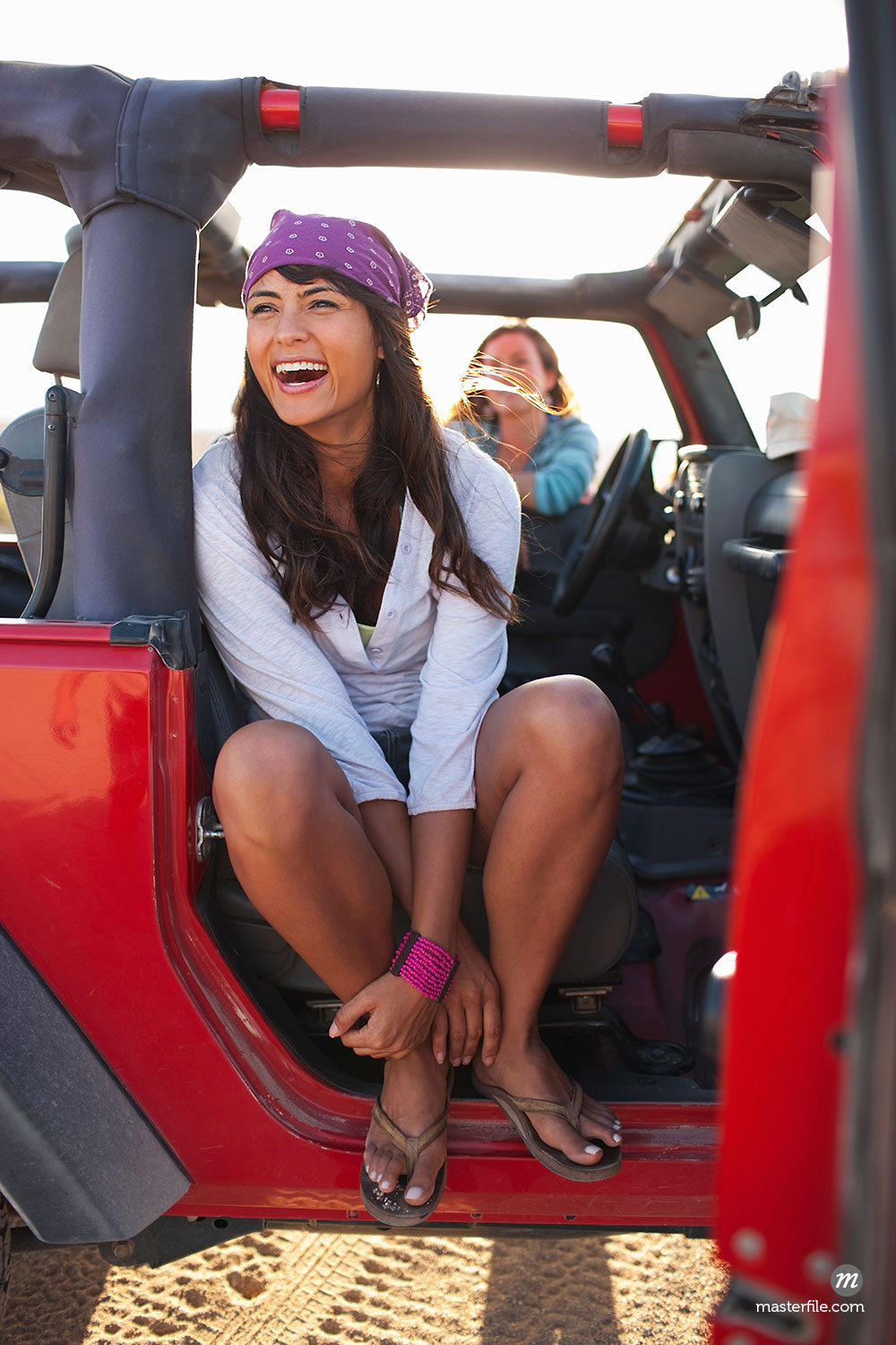 Women hanging out in red jeep in Baja California Sur, Mexico  ©  Ty Milford / Masterfile