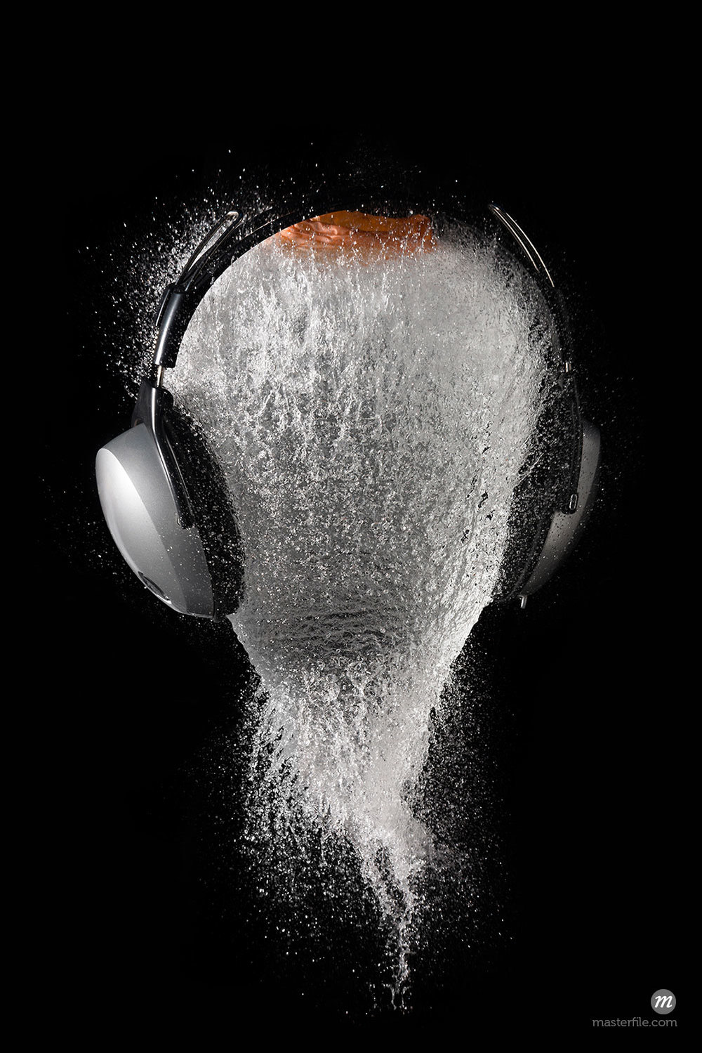 Conceptual image of the explosion of a head with headphones © Jose Luis Stephens / Masterfile