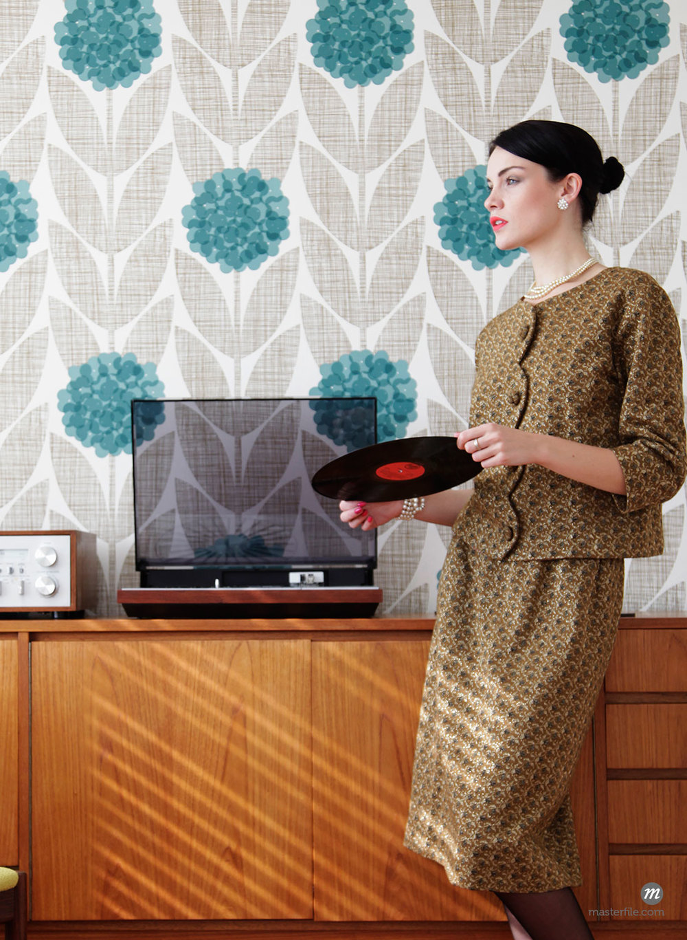Woman in vintage dress in mid-century modern living room with vinyl record  © Masterfile