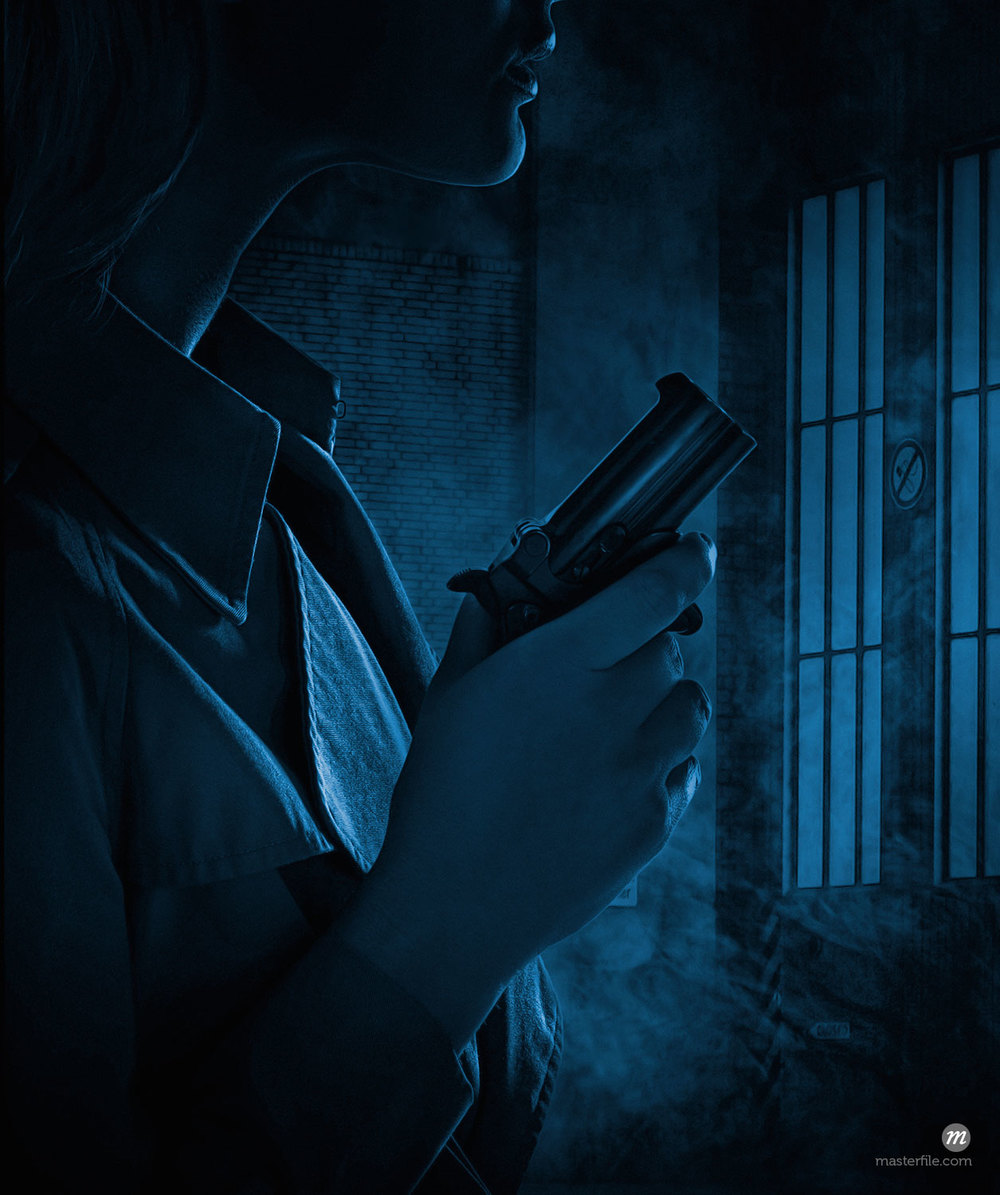 Silhouette of woman holding gun in dark room  © Masterfile