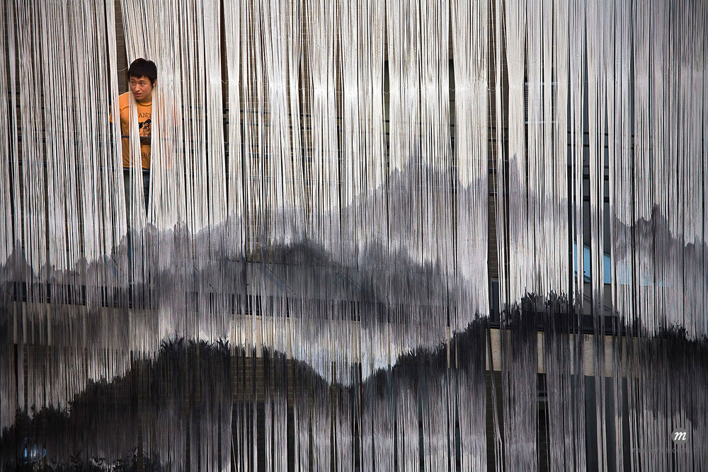 Man Looking through Hanging Tassels, Insadong, Seoul, South Korea  ©  R. Ian Lloyd / Masterfile