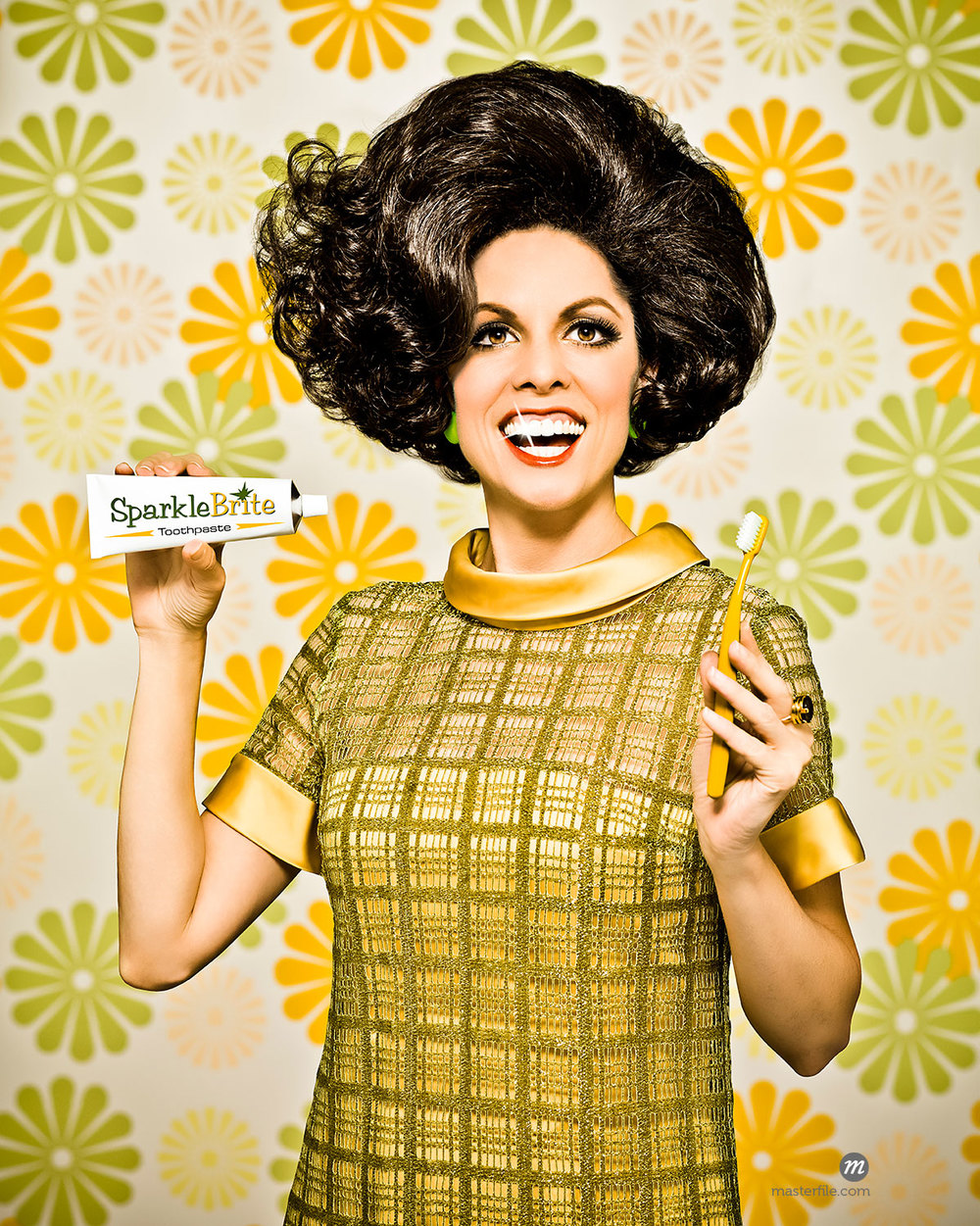 Woman in 1960's dress against 1960's flower wallpaper holding a toothbrush and tube of fictional toothpaste with a big smile and a sparkle on one tooth © Dana Hursey / Masterfile