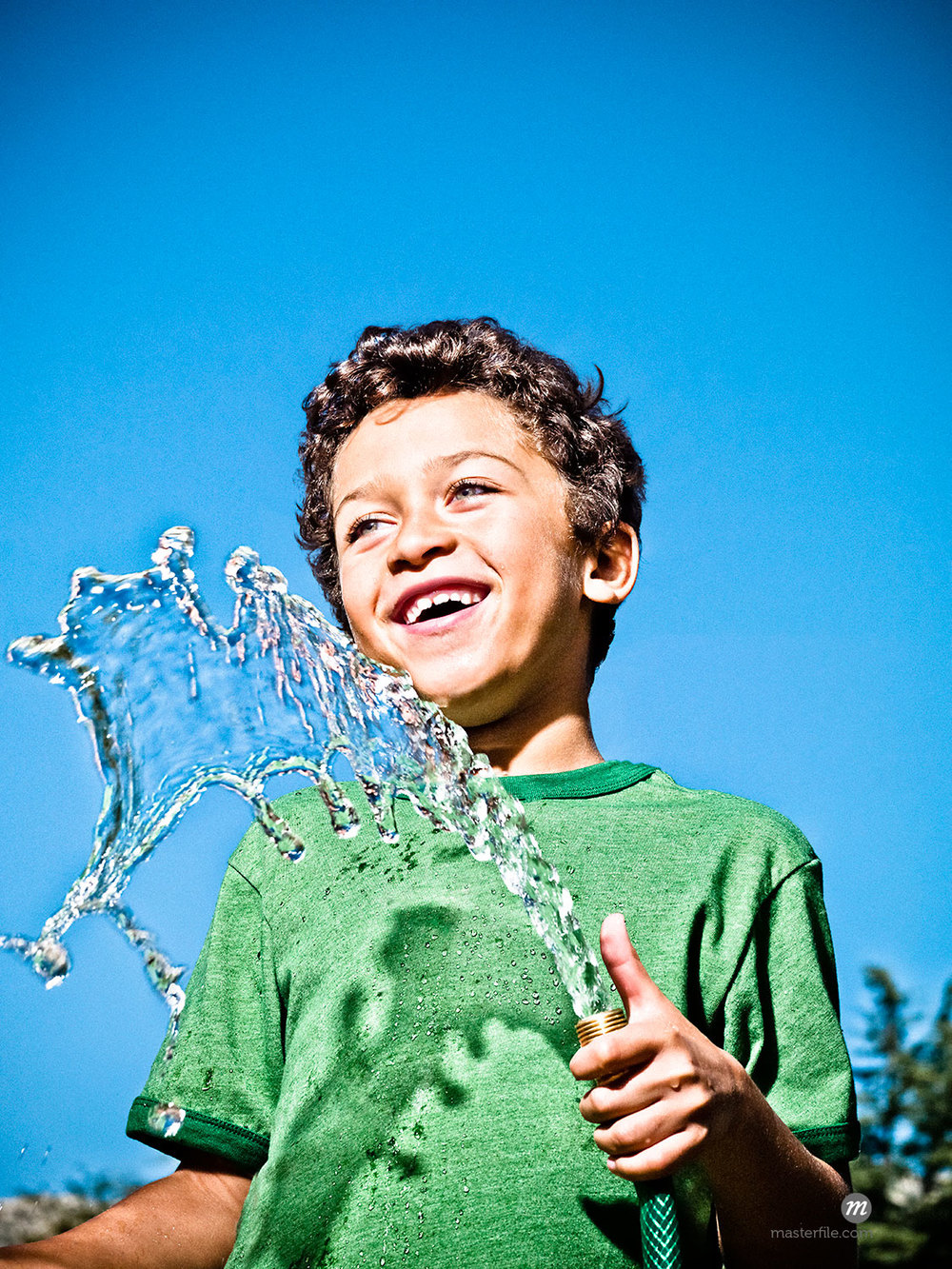 Boy in a green t-shirt holding running hose and smiling shot against a blue sky © Dana Hursey / Masterfile