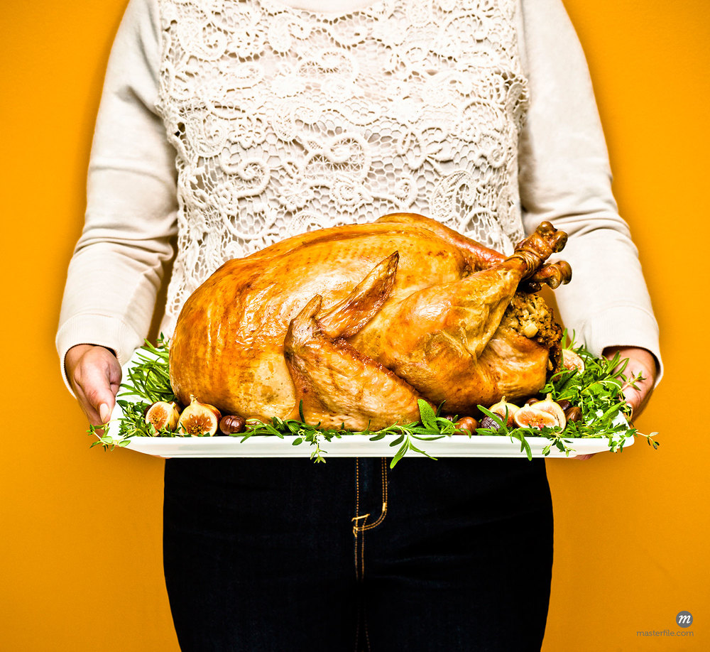Close-up of woman holding a platter with a stuffed turkey © Dana Hursey / Masterfile