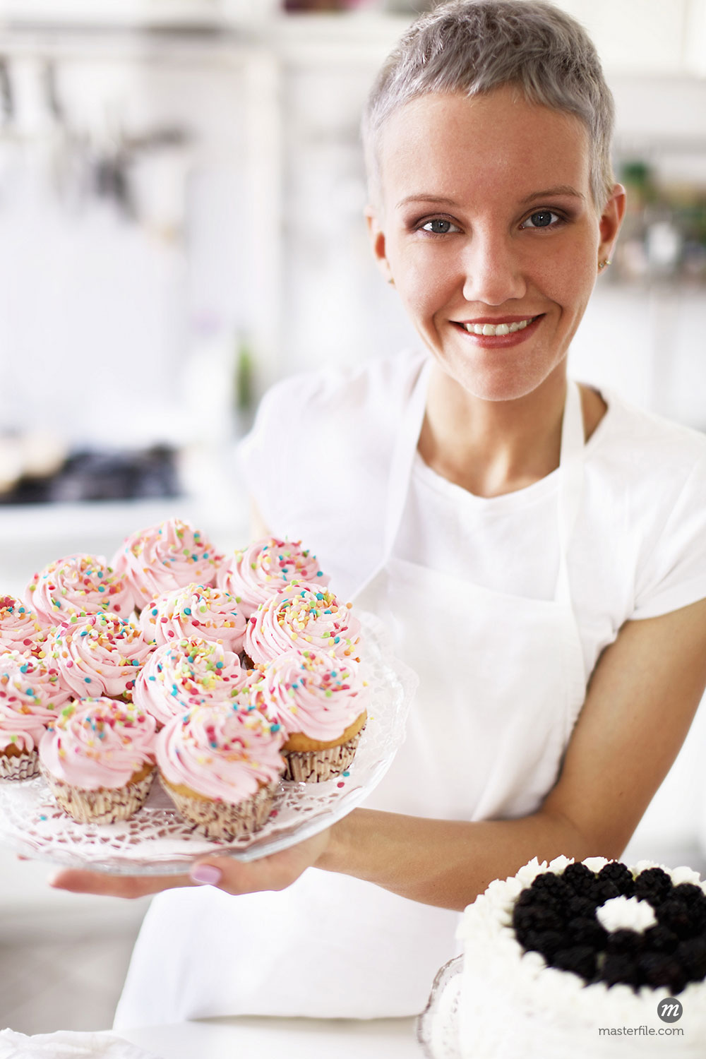 Portrait of woman holding hand made cupcakes  © Masterfile Royalty-Free