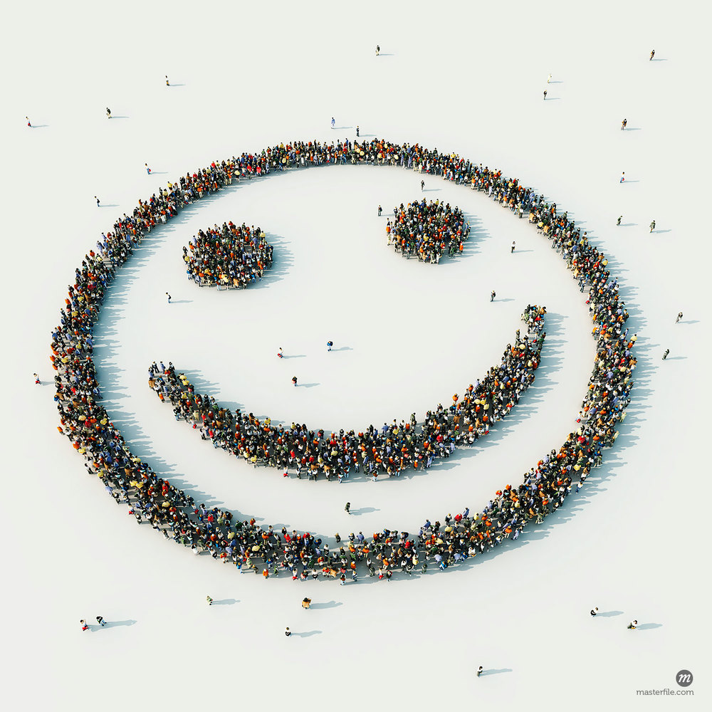 Aerial view of crowd of people arranged in smiley face © Ikon Images / Masterfile