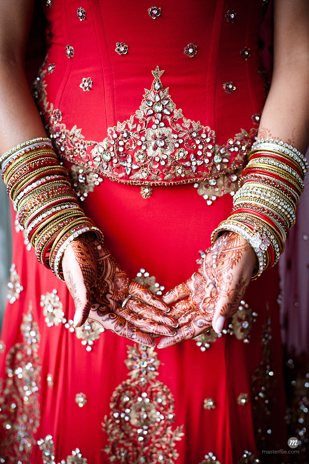 Hindu bride with henna design on hands at wedding ceremony © Ikonica / Masterfile