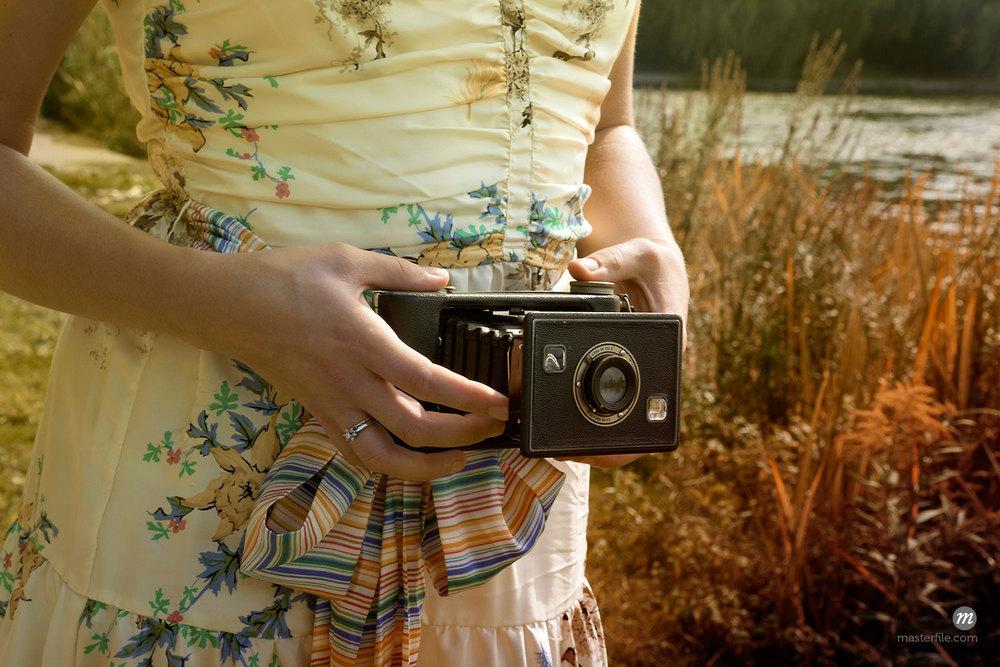 Woman Holding Folding Camera, High Park, Toronto, Ontario, Canada © Natasha Nicholson / Masterfile