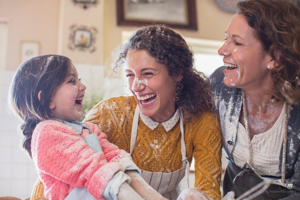 Three generations of women playing in the kitchen © Caia Image / Masterfile