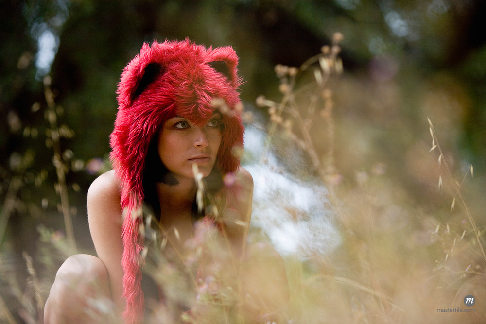 Woman Wearing Furry Hat Crouched in Long Grass  © Stellapictures / Masterfile