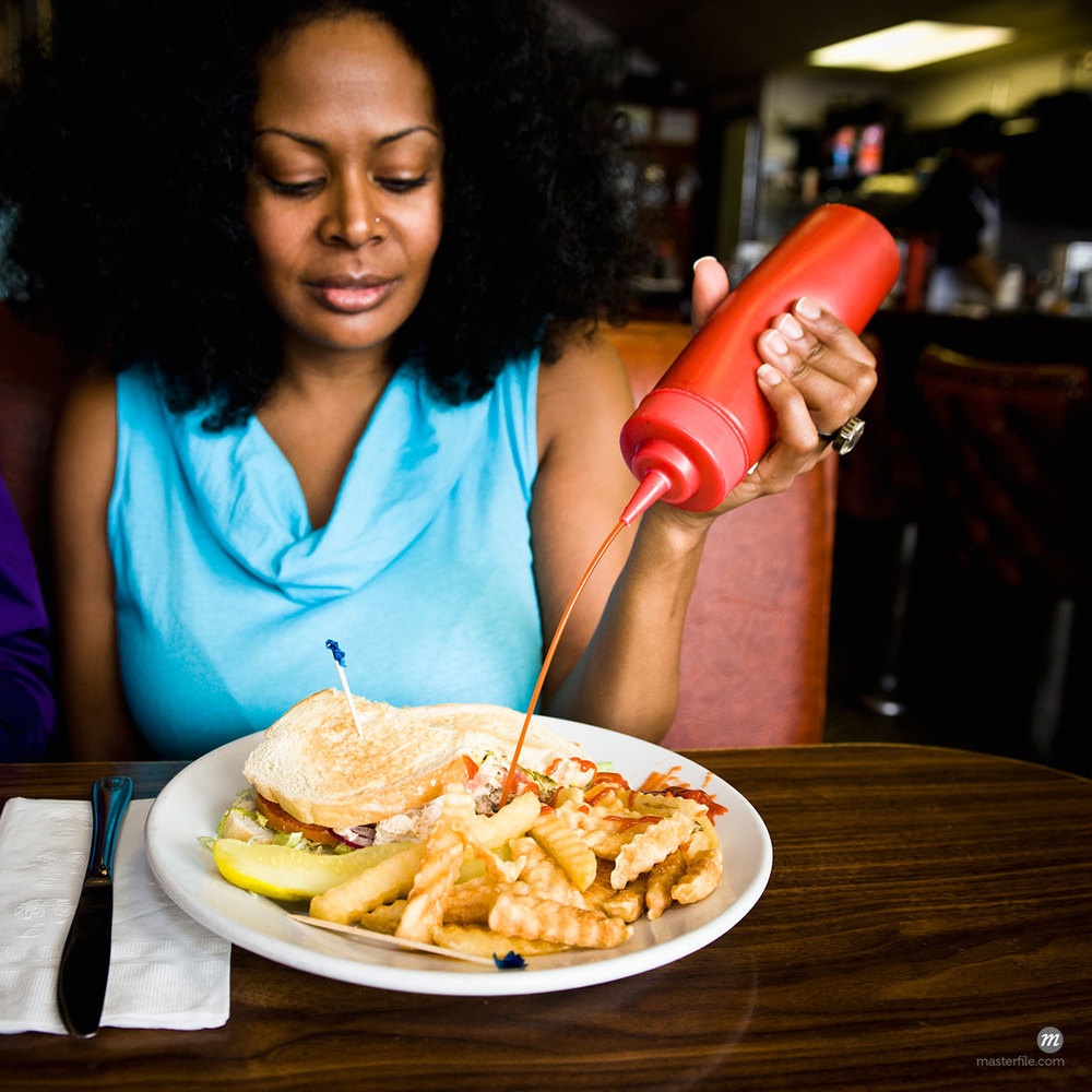 Woman squeezing ketchup on french fries in diner © Blend Images / Masterfile