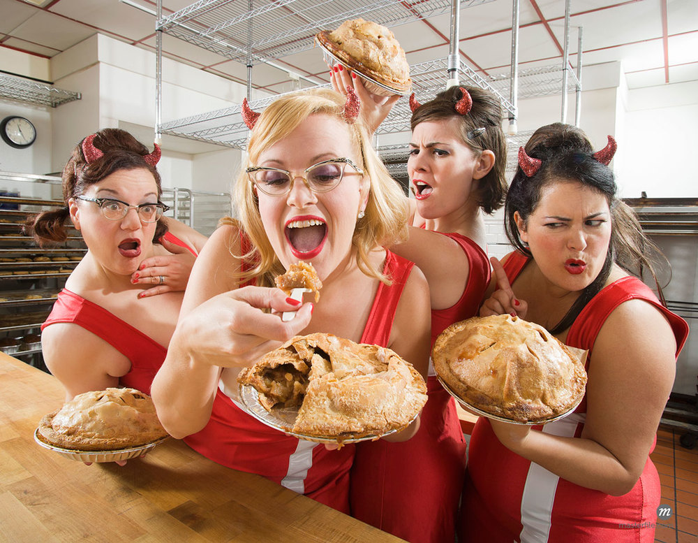 Women Wearing Devil Horns at a Bakery © Mitch Tobias / Masterfile