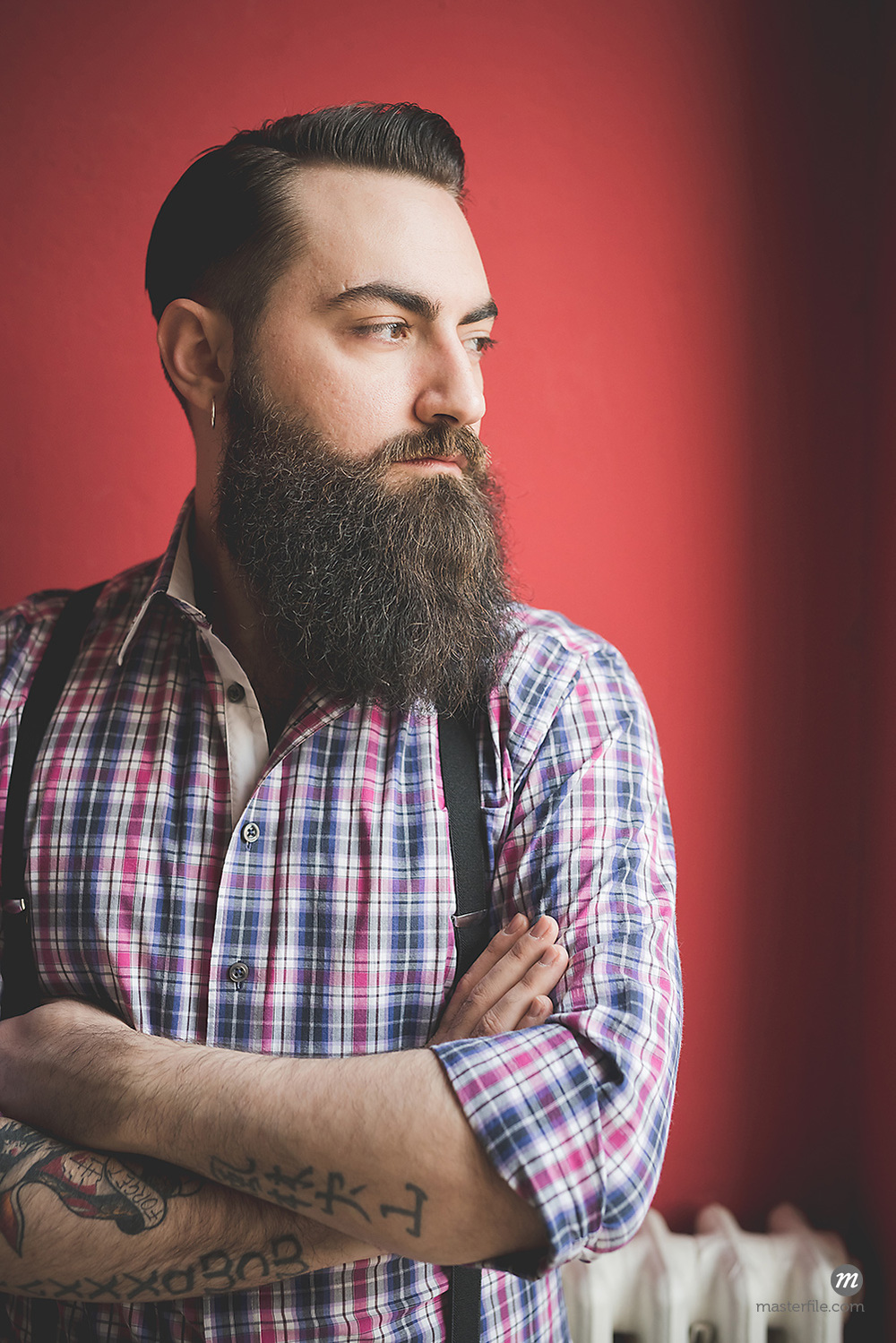 Portrait of young bearded man wearing plaid shirt and suspenders © Masterfile