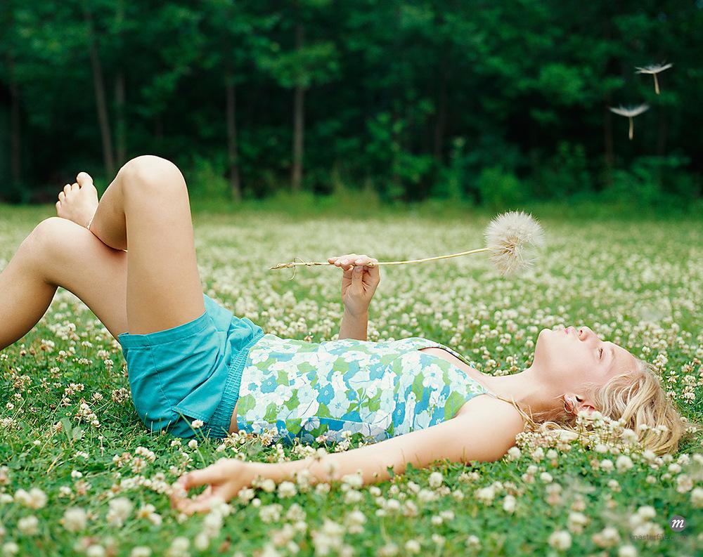 Girl Blowing Dandelion in Meadow © Susan Findlay / Masterfile