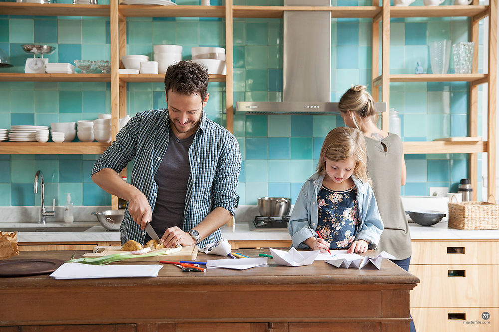 Young daughter drawing at kitchen counter while parents prepare meal  © Masterfile
