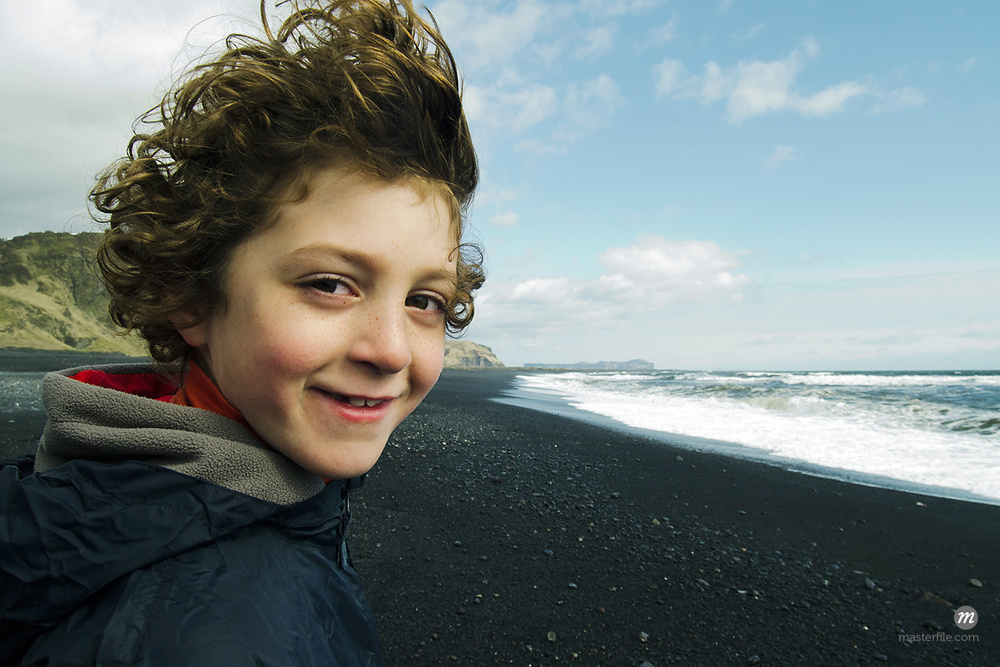 Portrait of a boy smiling on a beach in Iceland  © Masterfile