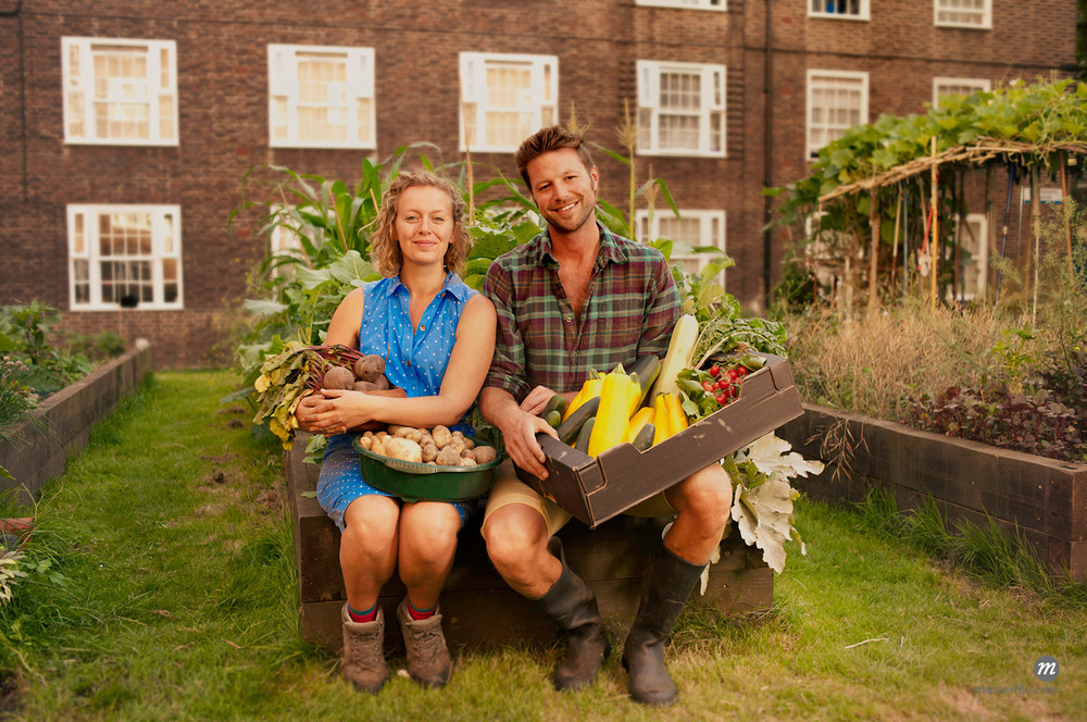 Couple Holding Harvested Vegetables on Council Estate Allotment © Masterfile Royalty-Free