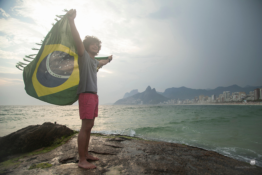 Young man standing on rock holding up Brazilian flag, Ipanema beach, Rio De Janeiro, Brazil  © Masterfile