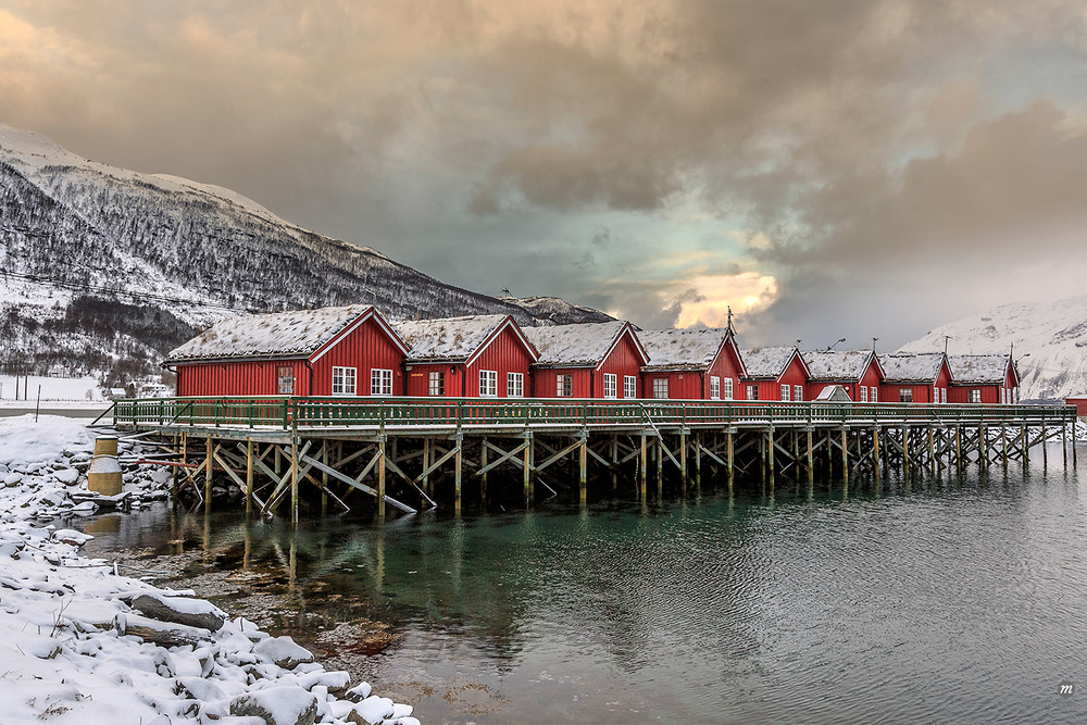 Traditional red wooden huts of fishermen in the snowy and icy landscape of Lyngen Alps, Troms, Lapland, Norway, Scandinavia, Europe © Masterfile