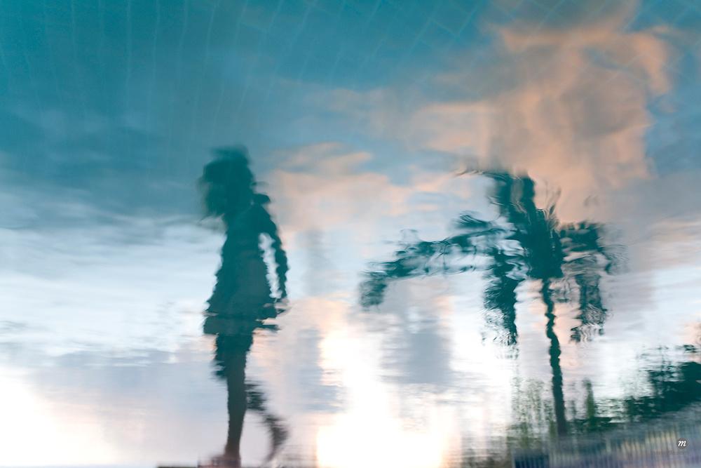 Reflection of woman walking alongside a pool © Michael Eudenbach / Masterfile