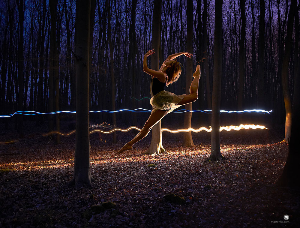 Female dancer leaping into the air in a darkened forest © Cultura RM / Masterfile