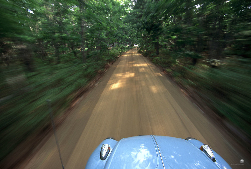 A 1974 VW Beetle drives along a tree-lined road in Permaquid, Maine, USA © Michael Eudenbach / Masterfile