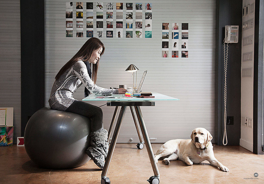 Japanese Woman Sitting on Exercise Ball in Home Office  © Masterfile