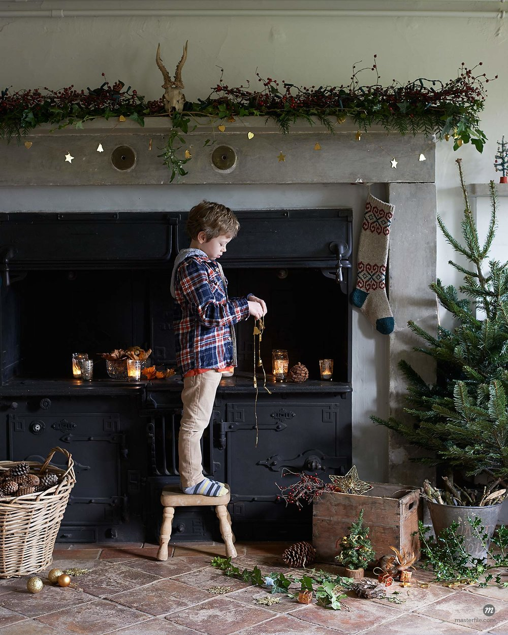 Boy decorating fireplace and mantel for Christmas © Masterfile